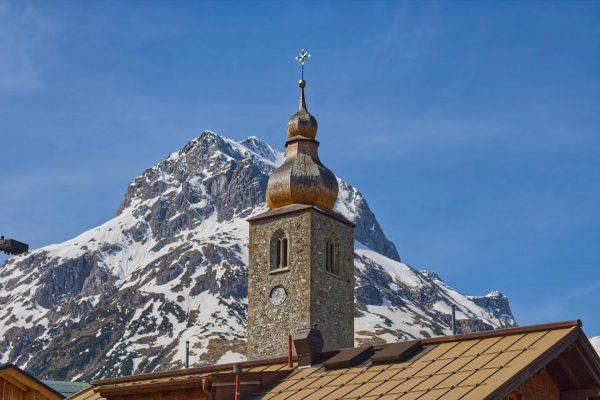 Der Turm der Pfarrkirche hl. Nikolaus in Lech am Arlberg. Im Hintergrund das ...
