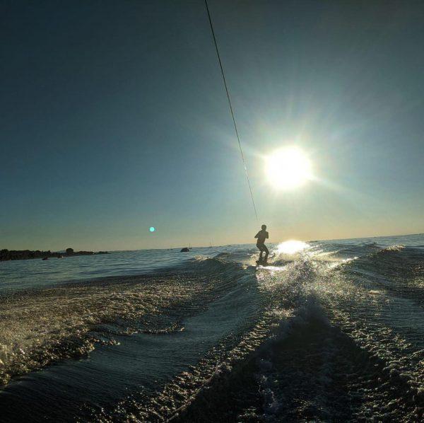 Mit dem Wakeboard von einem Boot über den Bodensee gezogen werden, während die ...