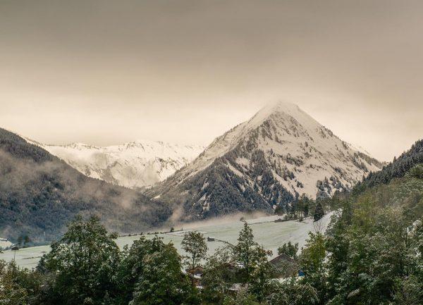 Der leichte Schneefall lässt die Wiesen und Wälder in ein zartes Grün tauchen. Der aufsteigende Dunst verstärkt...