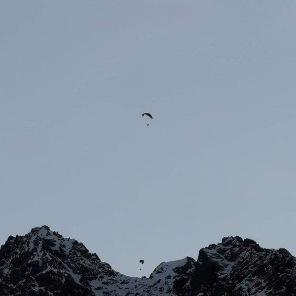 4 Paragleiter nützen noch die Gelegenheit und kreisen am abendlichen Himmel über der ...